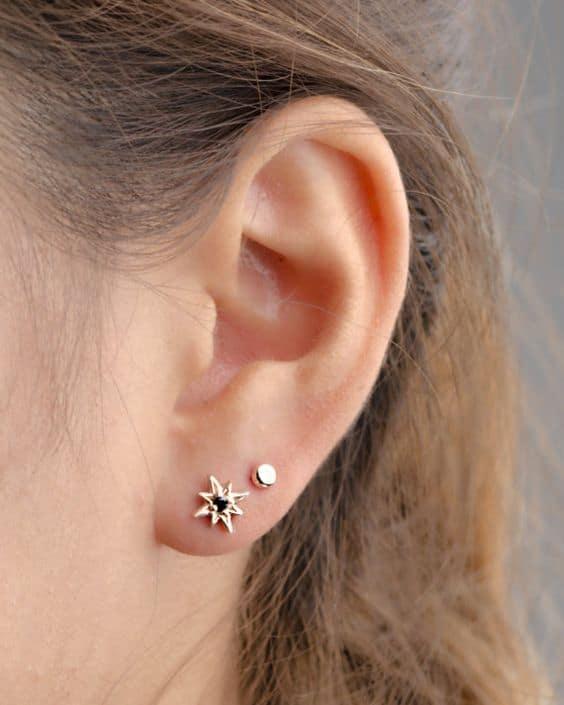 orelha com 2 furos e brincos dourados pequenos