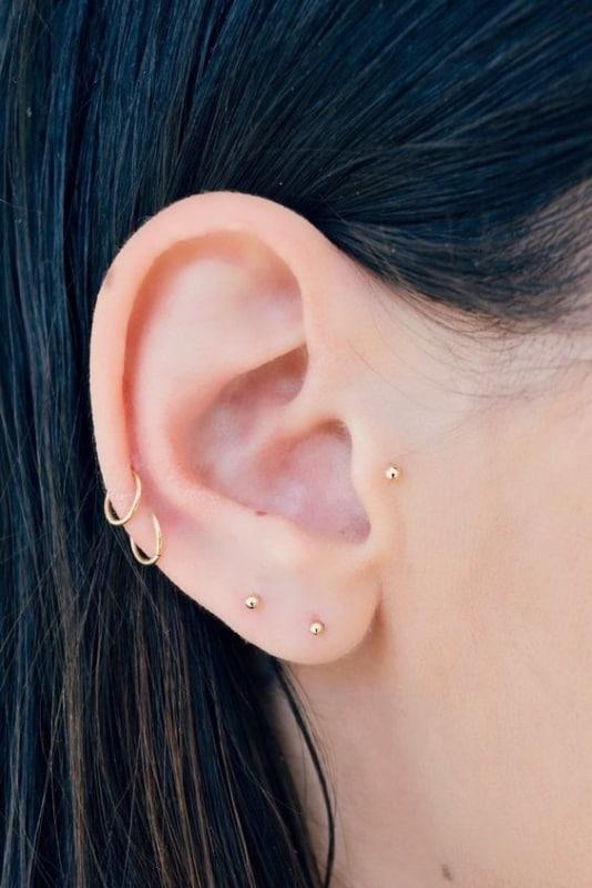 orelha com varios furos e brincos pequenos dourados