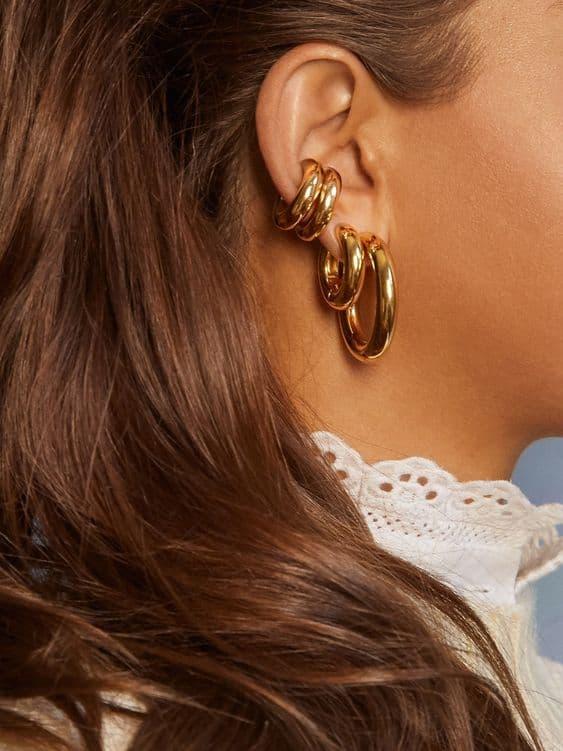 orelha com brincos dourados de argola