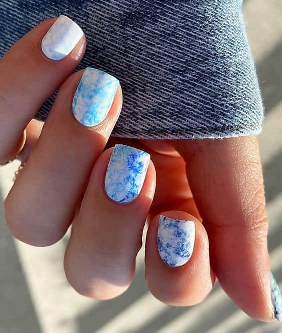 unhas decoradas com estilo tie dye azul e branco