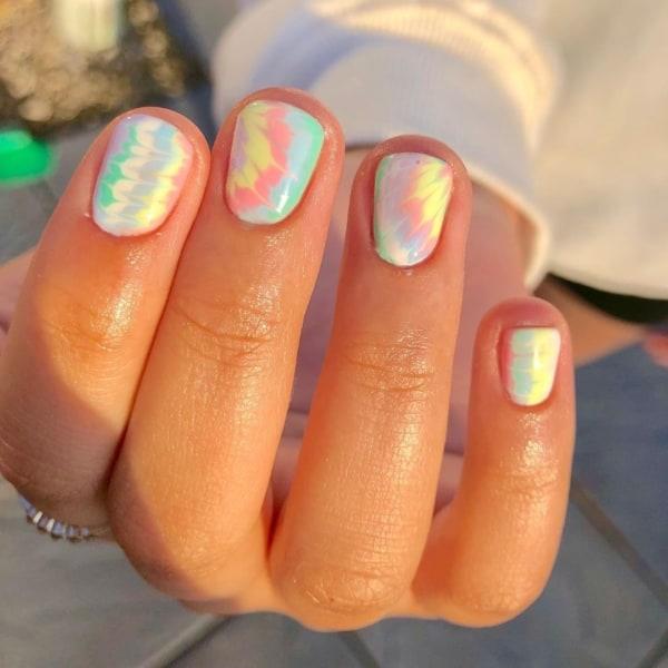 unhas curtas e redondas com tie dye em cores pastel