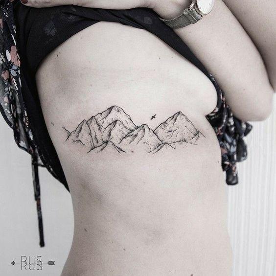 tatuagem feminina na costela com desenhos de montanhas