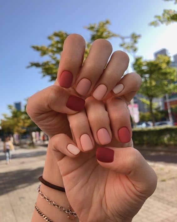unhas curtas decoradas cada uma de uma cor com esmalte fosco