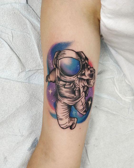 tatuagem de astronauta com fundo colorido de aquarela