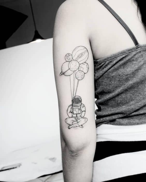tattoo preta e branca de astronauta com planetas