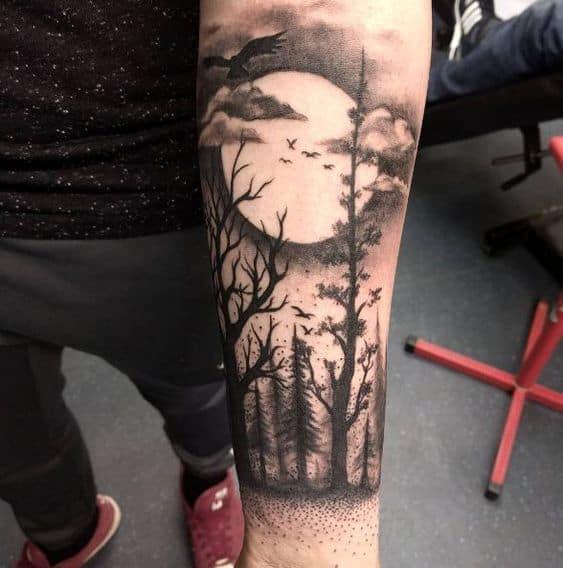 tatuagem de floresta negra com lua no braco
