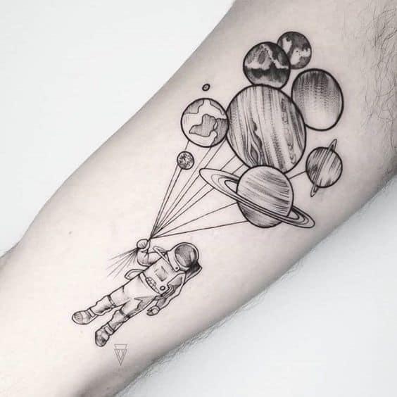 tatuagem de astronauta com planetas no braco