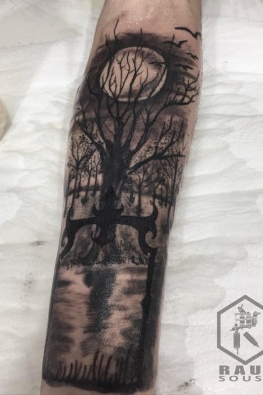 tattoo no braco de floresta e lua