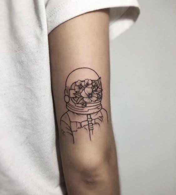 tatuagem feminina de astronauta com flores
