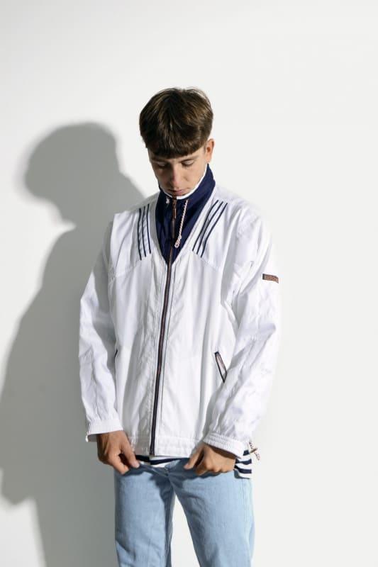 look masculino com jeans claro e corta vento branca