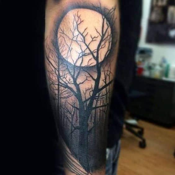tattoo no braco de floresta com lua