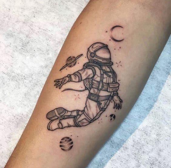 tatuagem feminina de astronauta com lua e planetas
