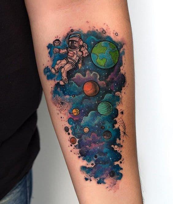 tatuagem feminina colorida de astronauta no braco