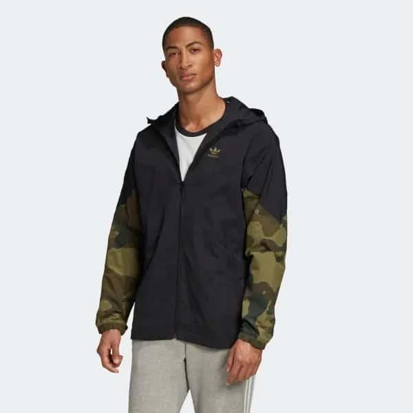 look masculino com calca cinza e corta vento com detalhes camuflados