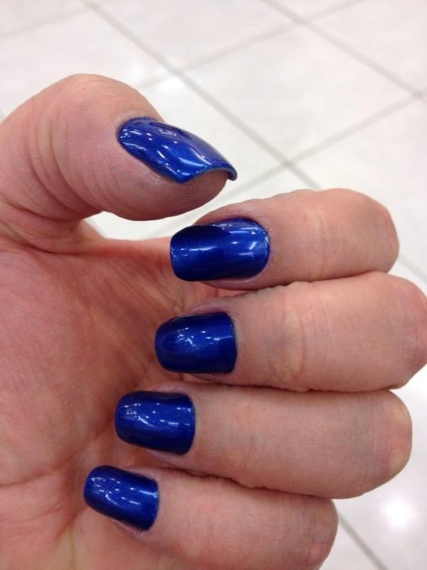 unha com esmalte azul escuro metalizado