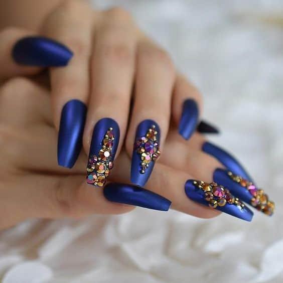 unhas decoradas com esmalte metalizado azul e joias