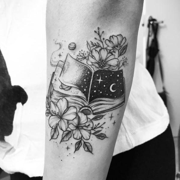 tatuagem de livro com universo e flores