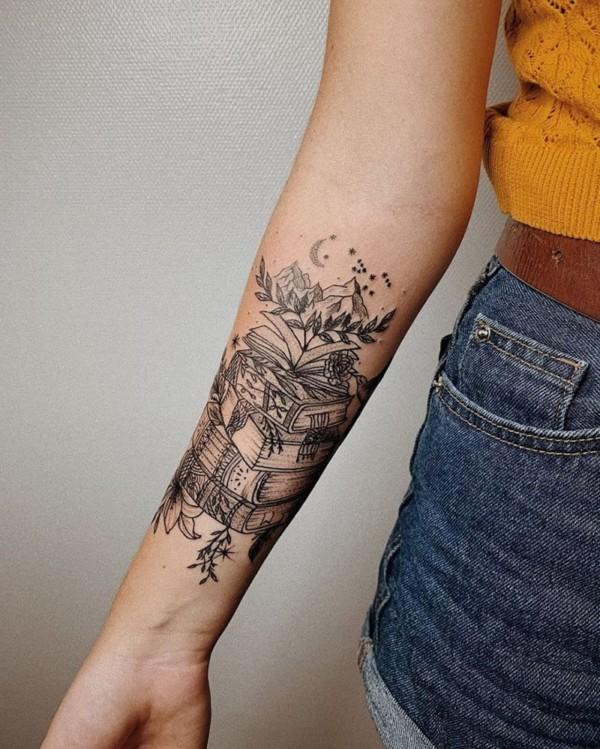 tatuagem de livros com montanhas ao anoitecer